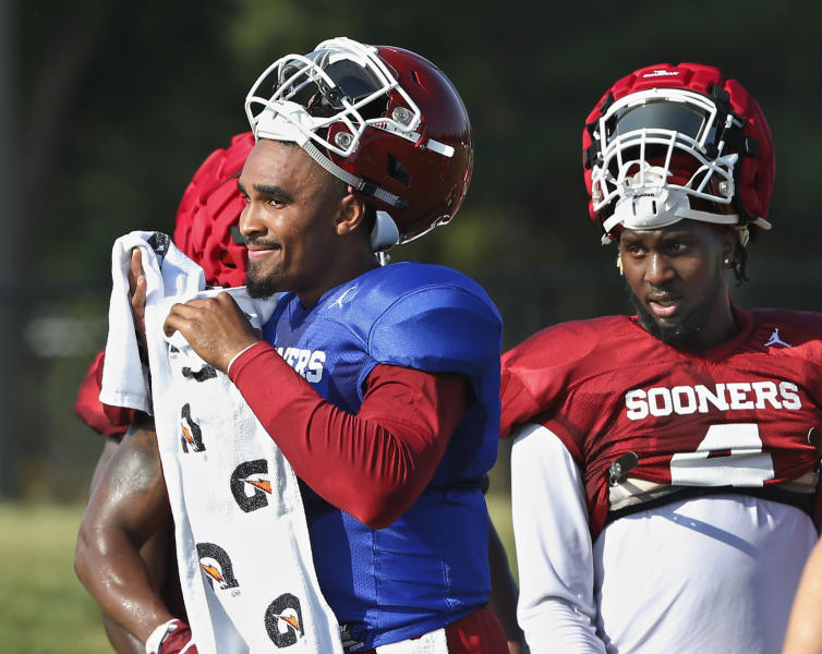 Oklahoma quarterback Jalen Hurts, left, and running back Trey Sermon, right, take a breather during an NCAA college football practice in Norman, Okla., Monday, Aug. 5, 2019. (AP Photo/Sue Ogrocki)