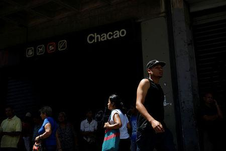 People walk past a closed metro station during a blackout in Caracas
