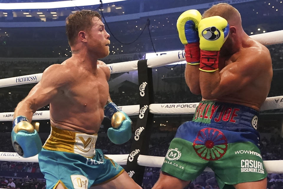 Canelo Alvarez, left, throws a punch against Billy Joe Saunders during a unified super middleweight world championship boxing match, Saturday, May 8, 2021, in Arlington, Texas.(AP Photo/Jeffrey McWhorter)