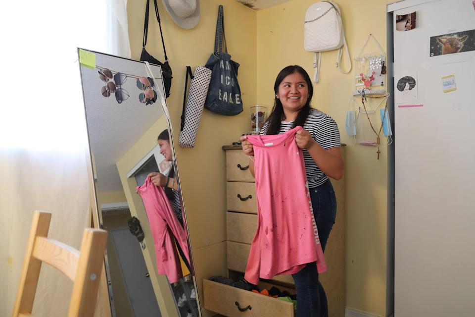 Luz Vazquez Hernandez, 18, pulls out the shirt she wore for roofing last summer. She helped her family by working during the pandemic while also attending school.