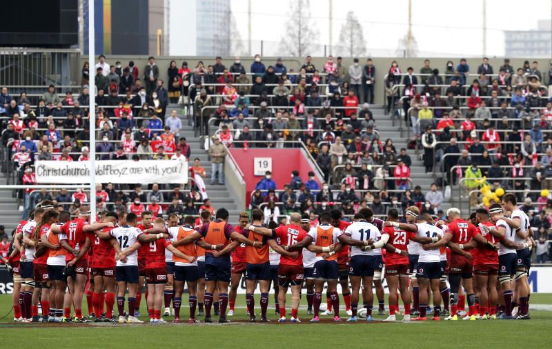 Players offer a silent prayer for the victims of Friday's mass shootings at two mosques in Christchurch, before their Super Rugby match between Sunwolves and Reds in Tokyo, Saturday, March 16, 2019. (AP Photo/Koji Sasahara)