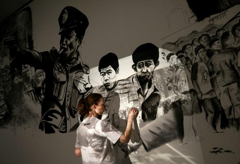 A local artist uses a projector to sketch a drawing in Tiravanija's installation