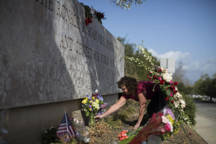 <p>Monika Poach arranges flowers left in memory of Nancy Reagan near the Ronald Reagan Presidential Library and Center for Public Affairs. <i>(Photo: David McNew/Getty Images)</i></p>