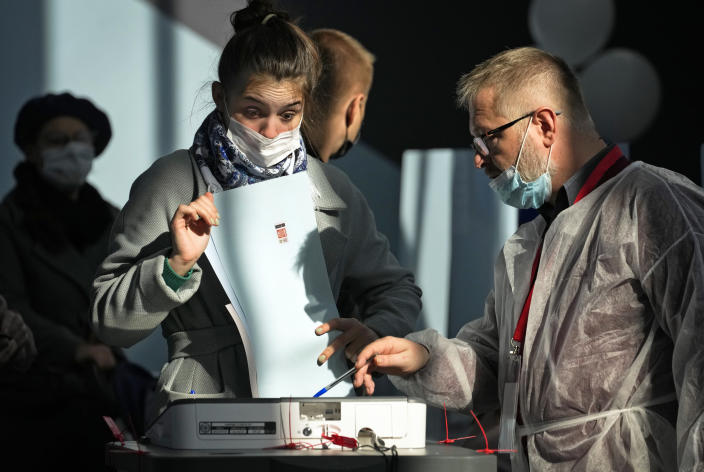 A member of an election commission helps to a woman to casts her ballot during the State Duma, the Lower House of the Russian Parliament and local parliament elections at a polling station in St. Petersburg, Russia, Sunday, Sept. 19, 2021. The head of Russia's Communist Party, the country's second-largest political party, is alleging widespread violations in the election for a new national parliament in which his party is widely expected to gain seats. (AP Photo/Dmitri Lovetsky)