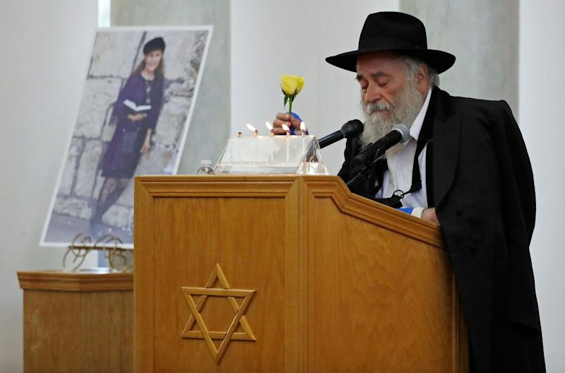 In this April 29, 2019 file photo, Yisroel Goldstein, Rabbi of Chabad of Poway, holds a yellow rose as he speaks at the funeral for Lori Kaye, who is pictured at left, in Poway, Calif.