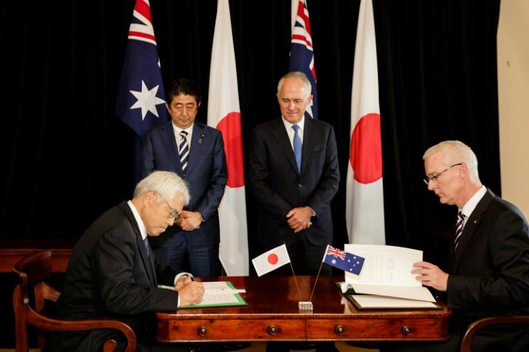 Japan's PM Shinzo Abe (L) and his Australian counterpart Malcolm Turnbull (R) watch as Japan's Ambassador to Australia Sumio Kusaka (front L) and Australia's Ambassador to Japan Bruce Miller sign an agreement in Sydney, on January 14, 2017