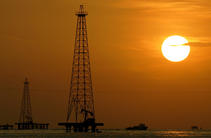 FILE - This Nov. 30, 2006 file photo shows oil drills in Maracaibo Lake in Venezuela's oil rich Zulia state. The Trump administration needs to decide by July 27, 2019 whether or not to allow Chevron to keep operating in Venezuela. (AP Photo/Leslie Mazoch, File)