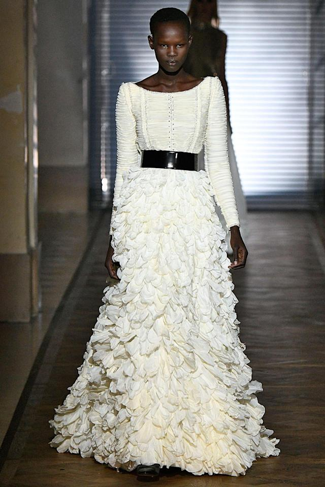 <p>Model wears a white, long-sleeved gown with petal appliqués from the Givenchy SS18 Haute Couture show. (Photo: Getty Images) </p>