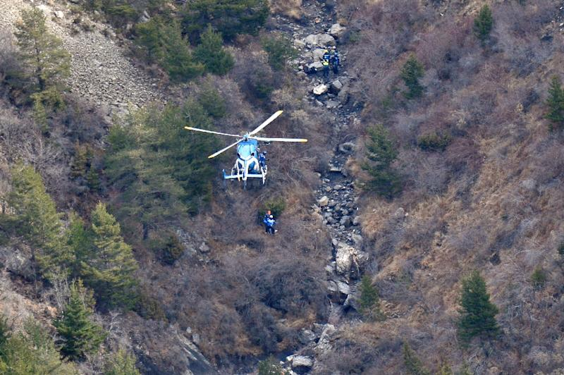 A helicopter and search-and-rescue personnel inspect the debris on March 25, 2015 close to where the Germanwings plane crashed in the French Alps