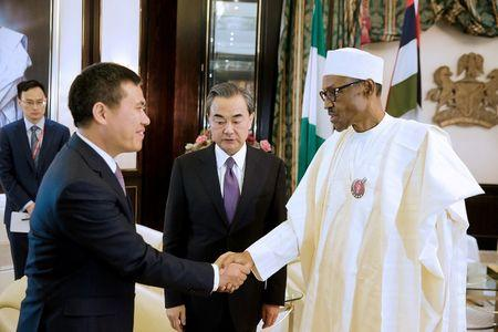 Nigeria's President Muhammadu Buhari greets China's Foreign Minister Wang Yi and Chinese Ambassador to Nigeria Zhou Pingjian during their visit to the Presidential Villa in Abuja