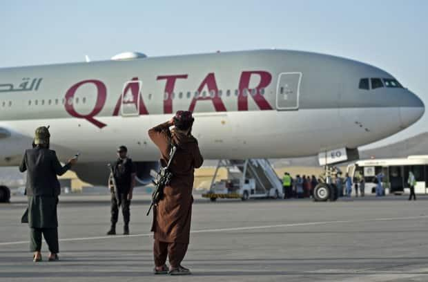 Qatari security personnel and Taliban fighters stand guard as passengers board a Qatar Airways aircraft at the airport in Kabul on September 9, 2021. (Wakil Kohasar/AFP/Getty Images - image credit)