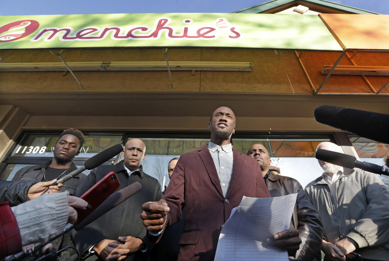 Byron Ragland addresses reporters in front of a frozen-yogurt shop Tuesday, Nov. 20, 2018, in Kirkland, Wash. The police department there has apologized for an incident in which officers helped the owner of the Menchie's shop expel Ragland, an African-American man, from the business because employees said they felt uncomfortable. The Seattle Times reported that the shop's owner called police on Nov. 7 about Ragland, who works as a court-appointed special advocate, who was in the shop supervising a court-sanctioned outing between a mother and her son. (AP Photo/Elaine Thompson)