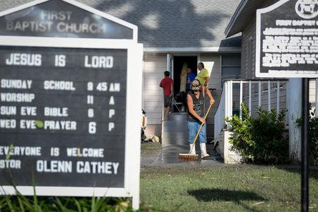 Residents clean up after Hurricane Irma heavily damaged the First Baptist Church in Everglades City, Florida, U.S., September 11, 2017. REUTERS/Bryan Woolston