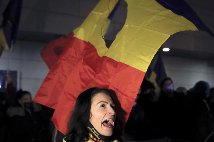 A woman shouts slogans during a protest outside the health ministry after a deadly fire at a hospital treating COVID-19 patients in Bucharest, Romania, Saturday, Jan. 30, 2021. Hundreds marched during a protest organized by the AUR alliance demanding the resignation of several top officials, after a fire early Friday at a key hospital in Bucharest that also treats COVID-19 patients killed five people. (AP Photo/Vadim Ghirda)
