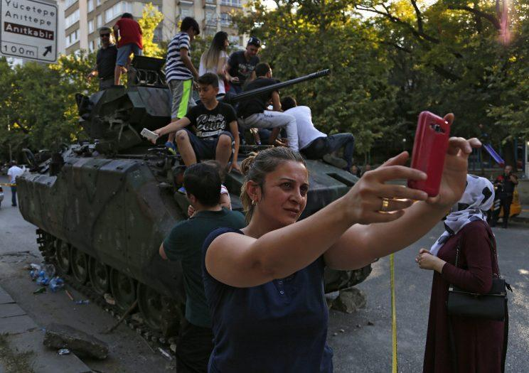 Taking selfies at a damaged armored personnel carrier that was attacked by protesters near the Turkish military headquarters in Ankara. (AP Photo/Hussein Malla)