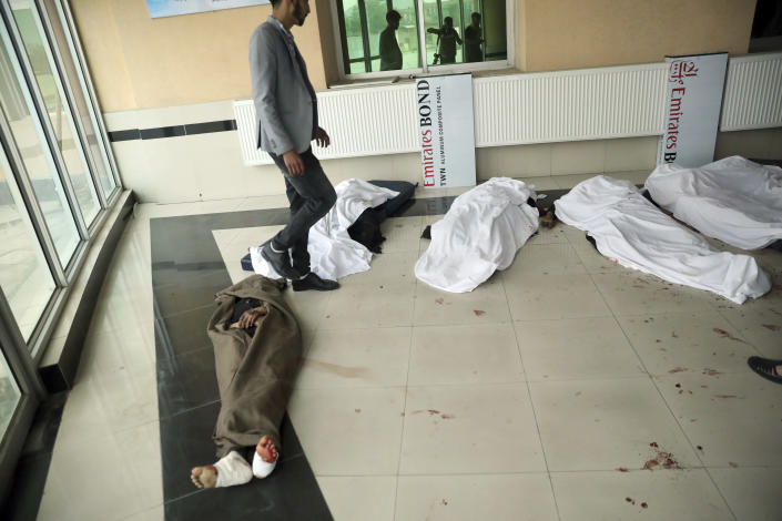 An Afghan man tries to identify the dead body at a hospital after a bomb explosion near a school in west of Kabul, Afghanistan, Saturday, May 8, 2021. A bomb exploded near a school in west Kabul on Saturday, killing several, many them young students, Afghan government spokesmen said. (AP Photo/Rahmat Gul)