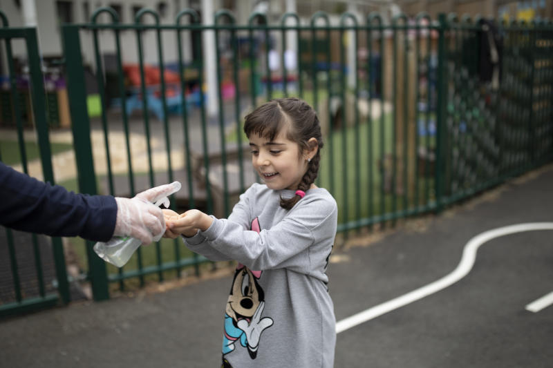 LONDON, ENGLAND - JUNE 04: A child is given hand sanitiser by a member of staff at the Harris Academy's Shortland's school on June 04, 2020 in London, England. As part of Covid-19 lockdown measures, Harris Academy schools have taught smaller pods of students, to help maintain social distancing measures. With restrictions now lifting and the Government encouraging schools to re-open, the school staff has been working to find the best way to provide extra spaces while still retaining the correct social distancing measures and cleanliness requirements. This week, some schools across England reopened for some students, with children in reception, Year 1 and Year 6 allowed to return first. (Photo by Dan Kitwood/Getty Images)