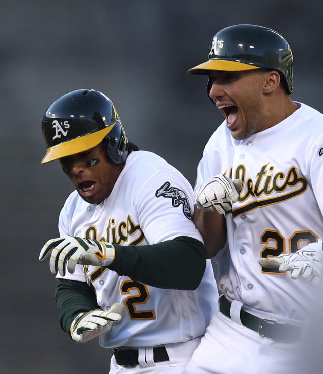 Oakland Athletics' Matt Olson, right, celebrates with Khris Davis after Olson drove in the winning run against the Chicago White Sox in the 14th inning of a baseball game Wednesday, April 18, 2018, in Oakland, Calif. (AP Photo/Ben Margot)