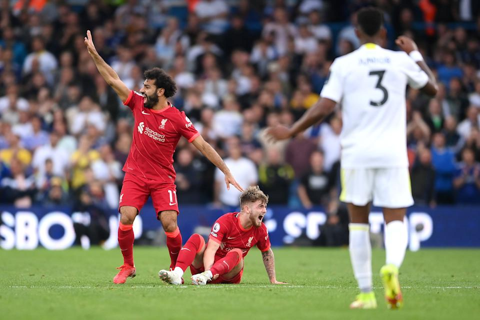 Harvey Elliott of Liverpool reacts as he looks to be injured as Mohamed Salah calls for medical attention.