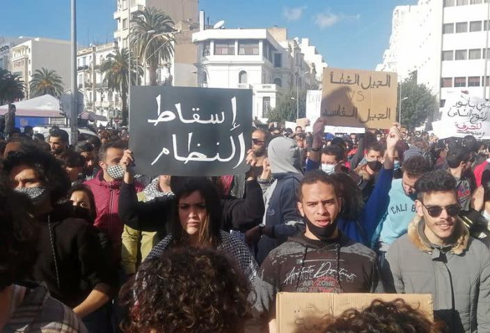 Demonstrators carry signs during an anti-government protest in Tunis
