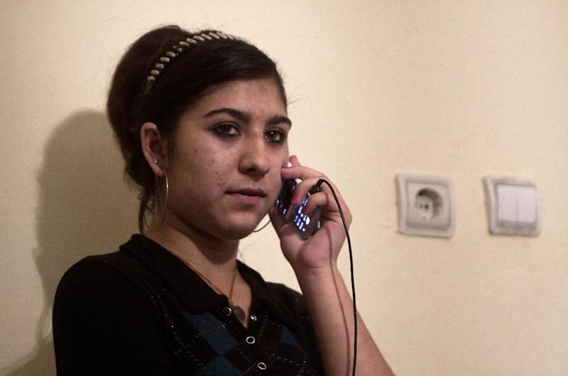 Maria Dibrani 17, expelled from France last week, talks on her mobile phone in a shelter house in Mitrovica, northern Kosovo Wednesday, Oct 16, 2013. France's government, trying to save face amid widespread outrage, said Wednesday that it is investigating the treatment of a 15-year-old girl of the Dibrani family who was detained by police in front of her fellow students so she and her family could be expelled to Kosovo as illegal immigrants. (AP Photo/Visar Kryeziu)