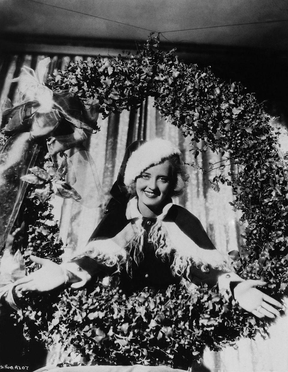 <p>Bette Davis does her best Santa Claus as she poses popping out of a Christmas wreath, circa 1930. Davis arrived in Hollywood in the early 1930s and quickly rose to fame after appearing in <em>Of</em> <em>Human Bondage</em> in 1934. </p>