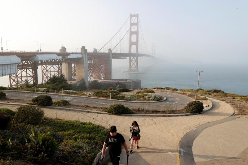 A couple walk up a trail with a hazy view of the Golden Gate Bridge, in San Francisco, California, last week.