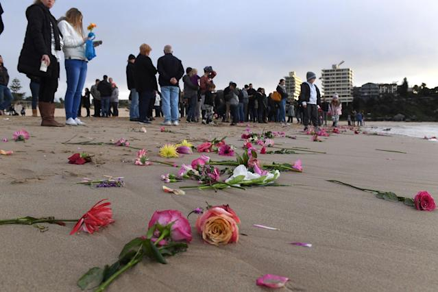 <p>Family and friends gather on Sydney's Freshwater Beach, Wednesday, July 19, 2017, following a candlelight vigil, where they threw hundreds of pink flowers into the ocean for Justine Damond who was shot by a Minneapolis police on July 15, 2017. (Photo: Dean Lewins/AAP Image via AP) </p>