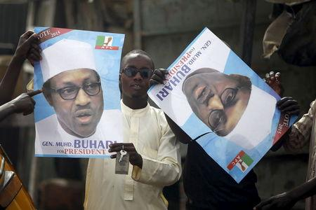 Supporters of presidential candidate Buhari hold his election posters in Kano