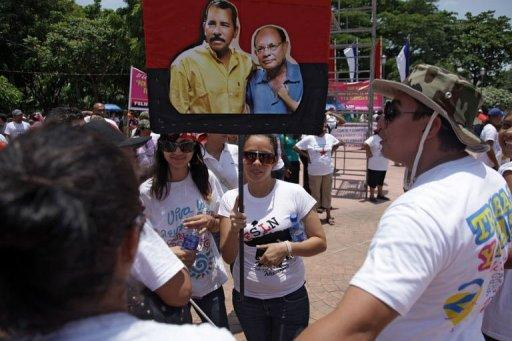 A woman holds a banner with the portrit of Nicaraguan President Daniel Ortega (L) and Tomas Borge
