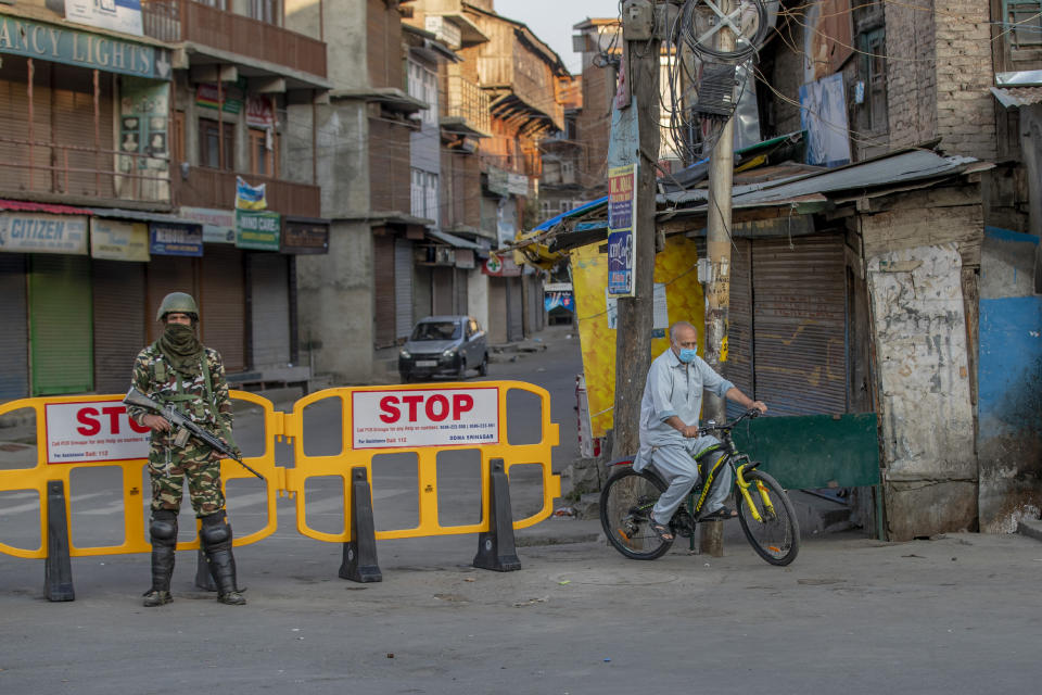 A Kashmiri cycles past a barricade set up as road blockade as a paramilitary soldier stands guard on the first anniversary of India's decision to revoke the disputed region's semi-autonomy, in Srinagar, Indian controlled Kashmir, Wednesday, Aug. 5, 2020. Last year on Aug. 5, India's Hindu-nationalist-led government of Prime Minister Narendra Modi stripped Jammu-Kashmir of its statehood and divided it into two federally governed territories. Late Tuesday, authorities lifted a curfew in Srinagar but said restrictions on public movement, transport and commercial activities would continue because of the coronavirus pandemic. (AP Photo/ Dar Yasin)