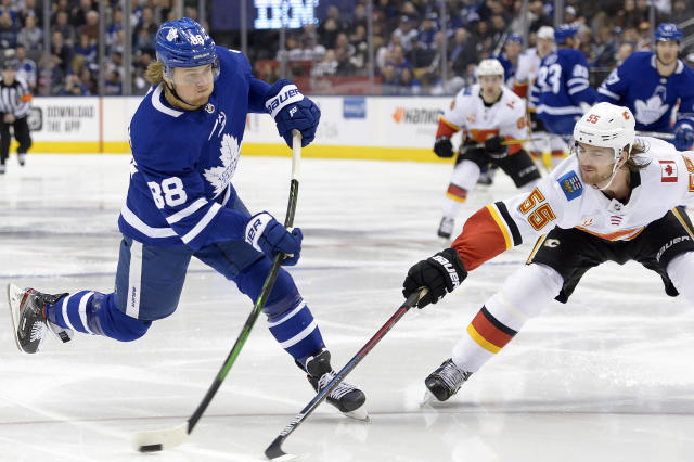 Toronto Maple Leafs right wing William Nylander (88) shoots past Calgary Flames defenseman Noah Hanifin (55) during the second period of an NHL hockey game Thursday, Jan. 16, 2020, in Toronto. (Nathan Denette/The Canadian Press via AP)