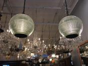 """This Oct. 15, 2019 photo shows salvaged two light fixtures reconfigured as pendant lamps from Paris street lamps, available for sale at Olde Good Things salvage store in New York. Two of the hottest trends in home decor are sustainability and authenticity. """"It's about both history and sustainability,"""" says Madeline Beauchamp of Olde Good Things, one of the oldest architectural salvage businesses in the country, with one shop in Los Angeles, another in Scranton, Pennsylvania, two stores in New York, and a flagship store to open soon in Midtown Manhattan. (Katherine Roth via AP)"""