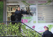 """Kosovo police officers enter a pharmacy in the northern Serb-dominated part of ethnically divided town of Mitrovica, Kosovo, Wednesday, Oct. 13, 2021. Serbian media reported an """"extremely tense"""" situation in the Serb-populated northern part of Mitrovica after Kosovo police raided a pharmacy and some shops in an apparent action to stop the smuggling of goods. (AP Photo/Bojan Slavkovic)"""