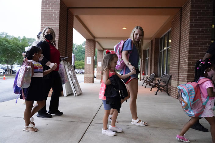 Students and parents walk to class at Tussahaw Elementary school on Wednesday, Aug. 4, 2021, in McDonough, Ga. Schools have begun reopening in the U.S. with most states leaving it up to local schools to decide whether to require masks. (AP Photo/Brynn Anderson)