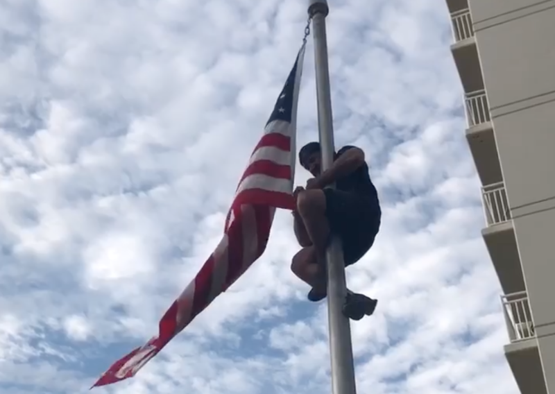 Dom Raso, a Navy SEAL, climbs a flagpole at a Navy SEAL monument in Virginia Beach in order to fix a wayward flag. (Photo: Facebook)