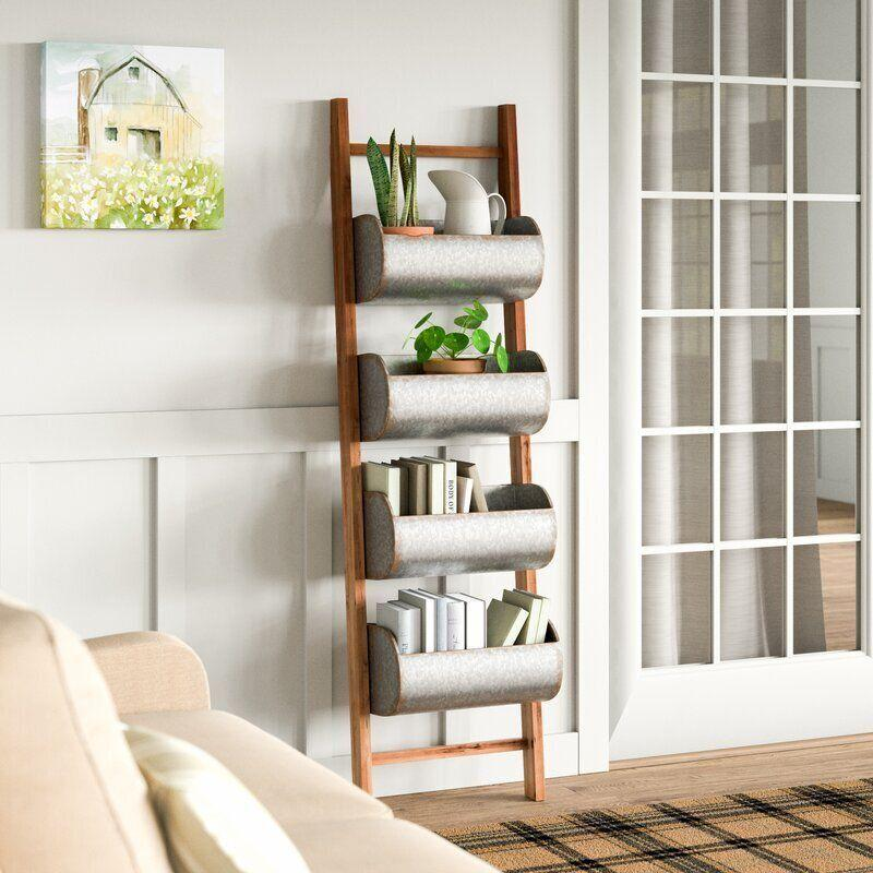 """Put away plants and books on thistiered ladder organizer, which comes with four storage bins. You can always hide away your knickknacks in here, too.<a href=""""https://fave.co/34b0njt"""" target=""""_blank"""" rel=""""noopener noreferrer"""">Find it for $188 at Wayfair</a>."""