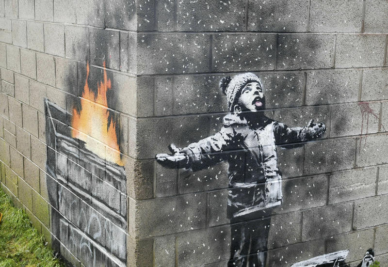 An artwork by Banksy on the side of a garage depicts a child dressed for snow playing in the falling ash and smoke from a skip fire, in Port Talbot, Wales. (Ben Birchall/PA FILE via AP)