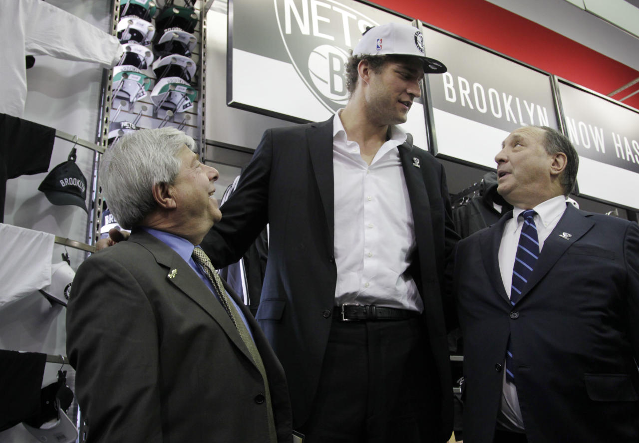 Brooklyn borough of New York president Marty Markowitz, left, Brooklyn Nets basketball team player Brook Lopez, center, and Barclay's Center developer Bruce Ratner talk after a news conference to unveil the new team logos in Brooklyn, Monday, April 30, 2012. The Nets will be moving from New Jersey to the new Barclays Center in Brooklyn for the 2012-2013 NBA basketball season. (AP Photo/Seth Wenig)