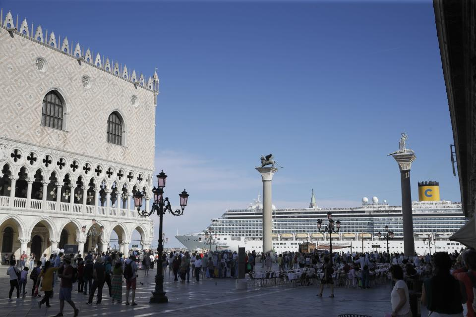 """FILE-- A cruise ship passes by St. Mark's Square in Venice, Italy, Sunday, June 2, 2019. Declaring Venice's waterways a """"national monument,"""" Italy is banning mammoth cruise liners from sailing into the lagoon city, which risked within days being declared an imperiled world heritage site by the United Nations. Culture Minister Dario Franceschini said the ban will take effect on Aug. 1 and was urgently adopted at a Cabinet meeting on Tuesday. (AP Photo/Luca Bruno)"""