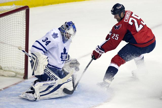 Toronto Maple Leafs goalie James Reimer (34) makes a save against Washington Capitals left wing Jason Chimera (25) during the third period of an NHL hockey game on Sunday, March 16, 2014, in Washington. The Capitals won 4-2. (AP Photo/ Evan Vucci)