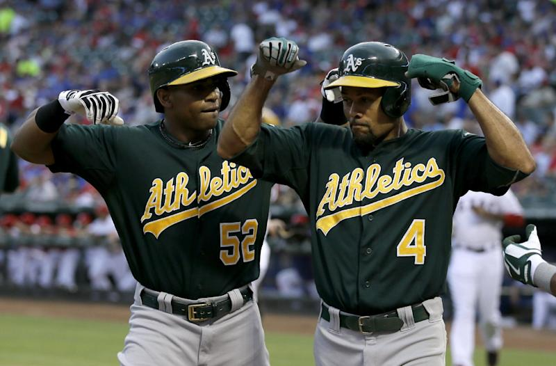Oakland Athletics' Yoenis Cespedes and Coco Crisp (4) flex their muscles as they walk back to the dugout following Cespedes' three-run home run that came off a pitch from Texas Rangers' Derek Holland in the first inning of a baseball game, Friday, Sept. 13, 2013, in Arlington, Texas. The shot scored Crisp and Josh Donaldson. (AP Photo/Tony Gutierrez)