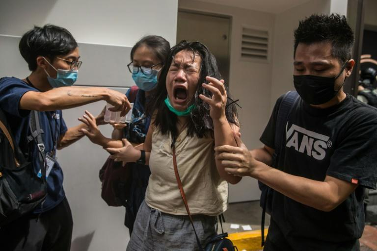 A woman reacts after being hit by pepper spray as police tried to stop protests in Hong Kong