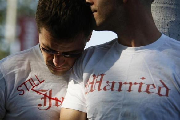 Gay couple Ethan Collings (L), 32, and his spouse Stephen Abate, 36, hug as they celebrate their one-year wedding anniversary in West Hollywood, California, June 16, 2009. The couple were married when same-sex marriages were first allowed last year.