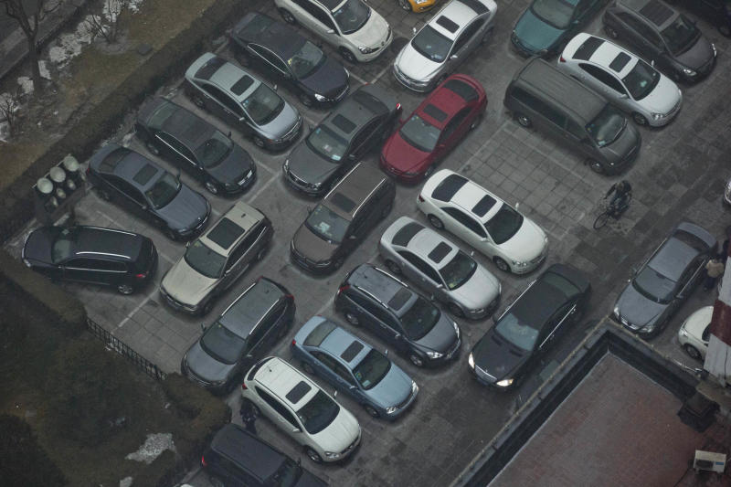 In this photo taken Thursday, Jan. 31, 2013, cars are cramped into a parking lot during a day of heavy pollution in Beijing, China. China plans to increase the number of cities that restrict vehicle purchases in a bid to fight pollution and traffic congestion, state media reported Thursday, July 11, 2013. With more than 13 million cars sold in China last year, motor vehicles and their emissions have emerged as the chief culprit for the air pollution in large cities. (AP Photo/Ng Han Guan)