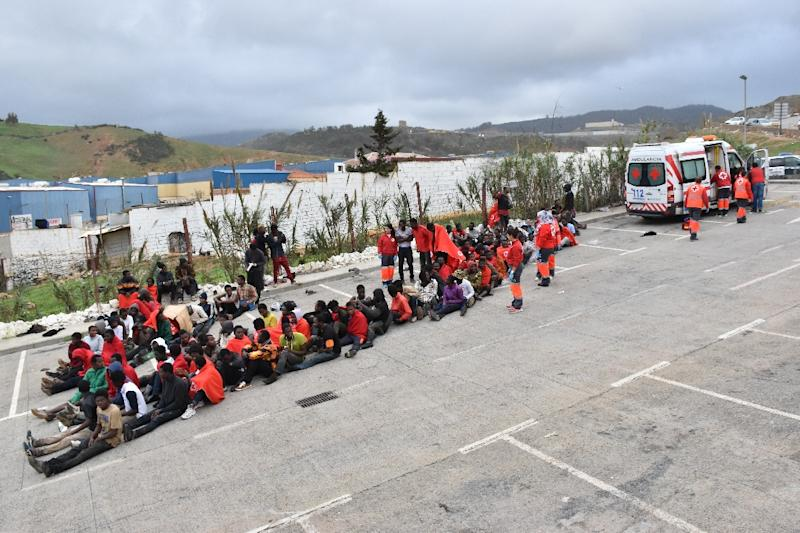 Migrants pictured on the ground in El Tarajal, Ceuta, close to the border with Morocco on December 9, 2016 after being rounded up by police to be attended to by Red Cross personnel