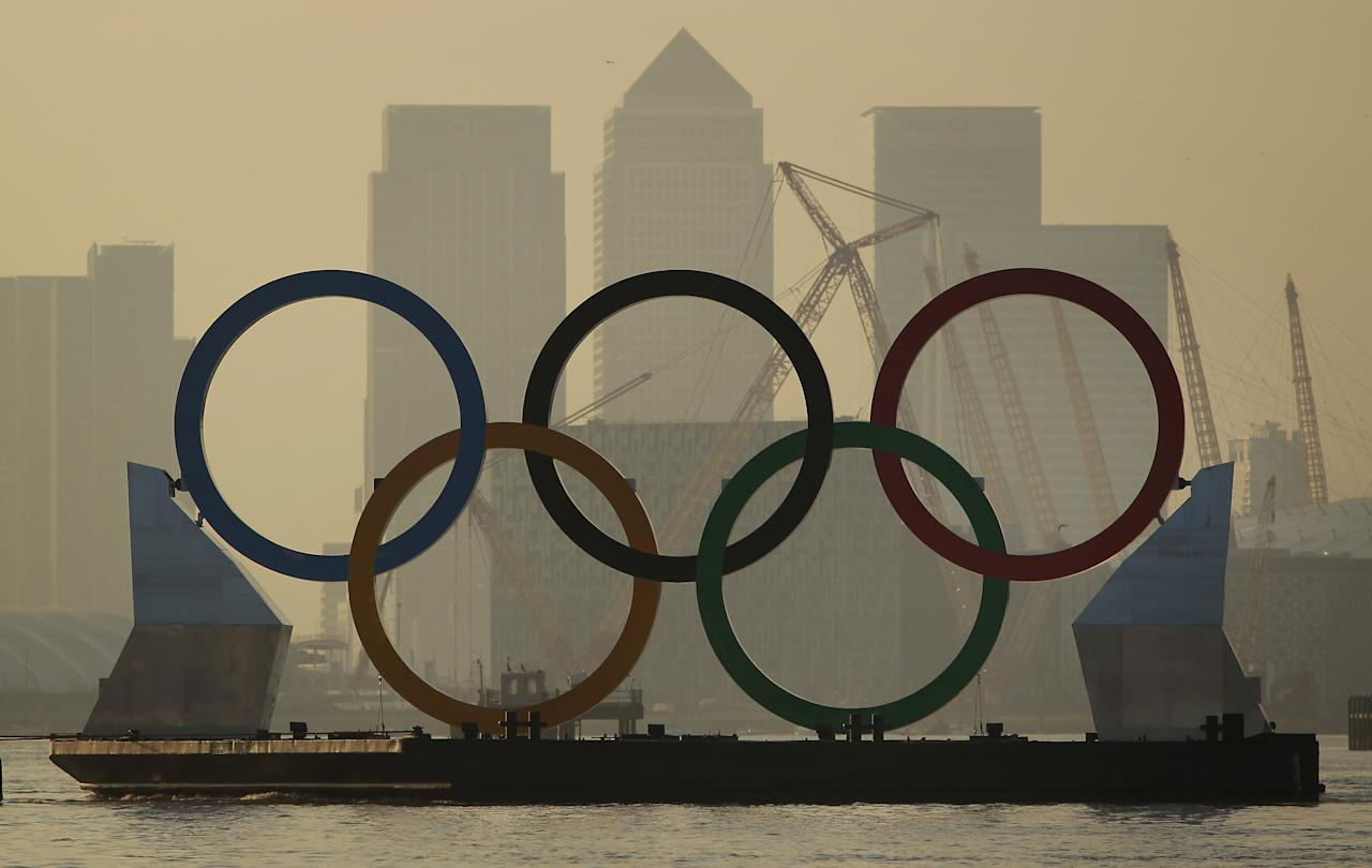 LONDON, ENGLAND - FEBRUARY 28:  Giant Olympic rings are towed on The River Thames in site of the O2 arena (R) and Canary Wharf financial district on February 28, 2012 in London, England. With 150 days remaining before the start of the London 2012 games the Olympic rings, measuring 11 metres high by 25 metres wide, are being showcased on the river as Mayor of London Boris Johnson is announcing details of two new cultural programmes, which will be part of the London 2012 Festival, along with details of other cultural events being organised to celebrate the London 2012 Olympic and Paralympic Games.  (Photo by Peter Macdiarmid/Getty Images)