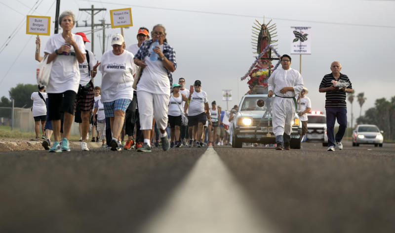 Alter server Anthoney Saenz, second from right, waves incense as he helps lead a procession toward the Rio Grande to oppose the wall the U.S. government wants to build on the river separating Texas and Mexico, Saturday, Aug. 12, 2017, in Mission, Texas. The area would be the target of new barrier construction under the Trump administration's current plan. (AP Photo/Eric Gay)