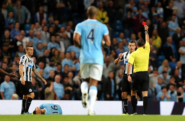 Newcastle United's Steven Taylor is shown a red card by referee Andre Marriner after a foul on Manchester City's Sergio Aguero (floor)