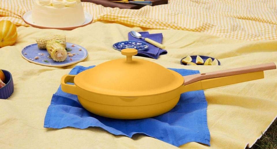 The Always Pan in zest, a bright yellow lays on a picnic. (Image via Our Place)
